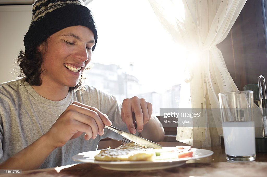 Young Male Skier Enjoying Food In Bansko Chalet : Stock Photo