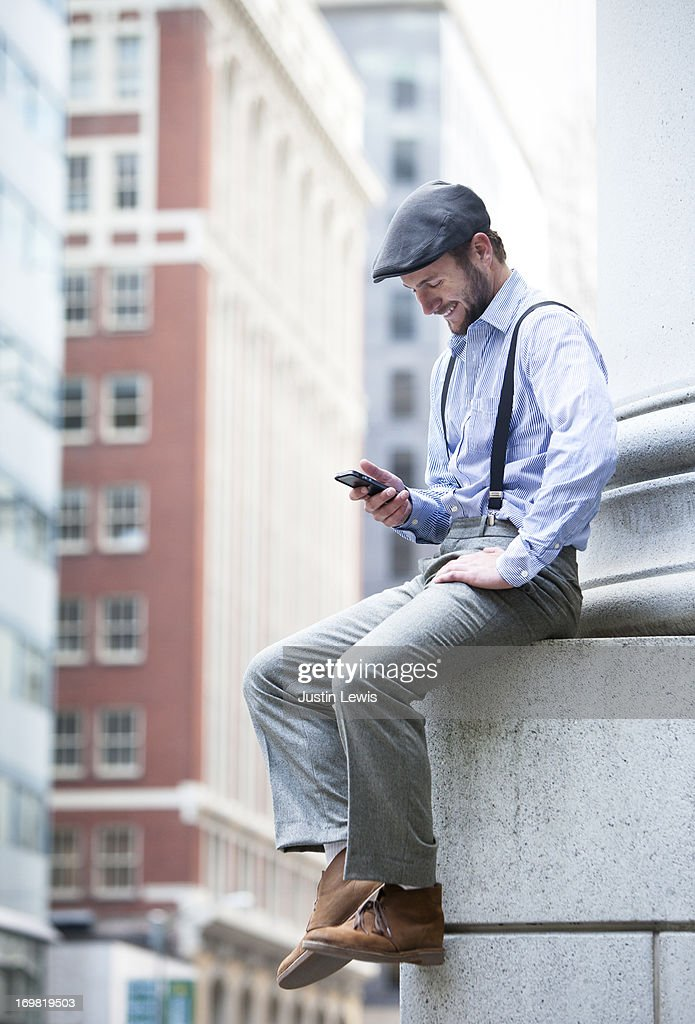 Young male smiling while texting in the city