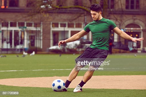 Young male soccer player kicking ball on soccer pitch