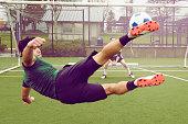 Young male soccer player kicking ball toward goal