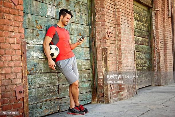Young male soccer player texting on smartphone