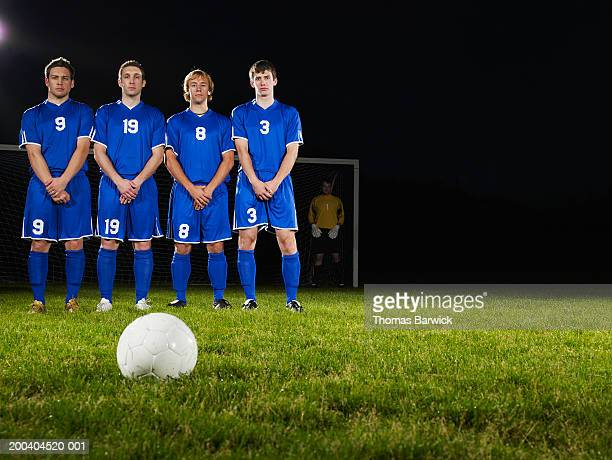Young male soccer players in defensive wall, awaiting free kick