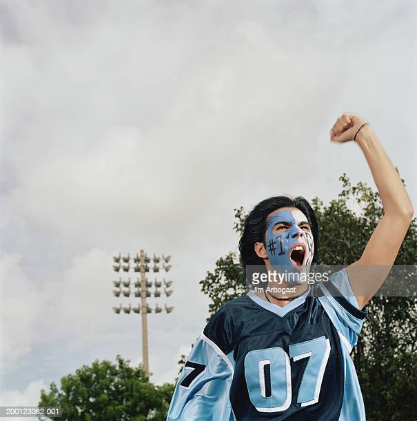Young male sports fan with painted face, cheering and pumping fist