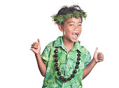 This Hawaiian child with missing front teeth offers an open mouth smile and a 'shaka' hand gesture to spread the spirit of Aloha  Isolated on white