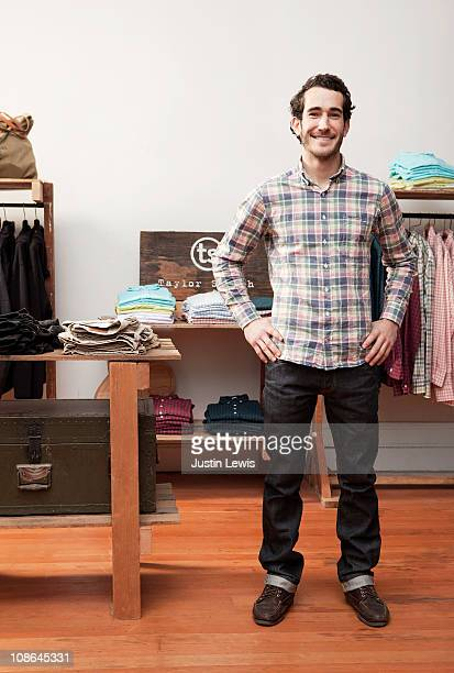 Young male standing happily in clothing store