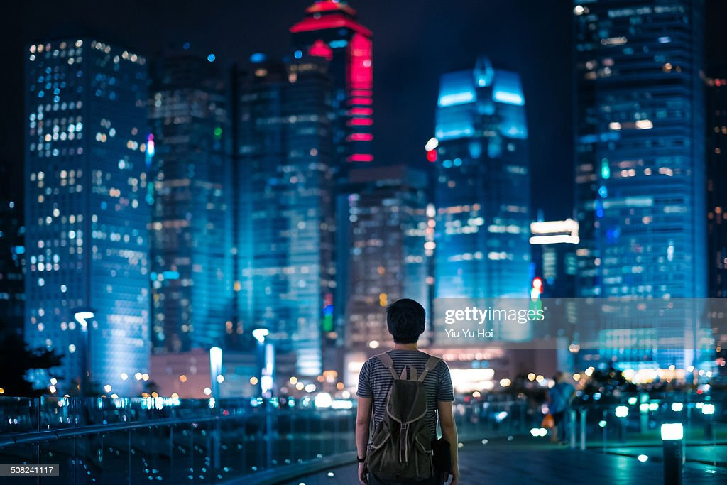 Young male standing in front of modern city