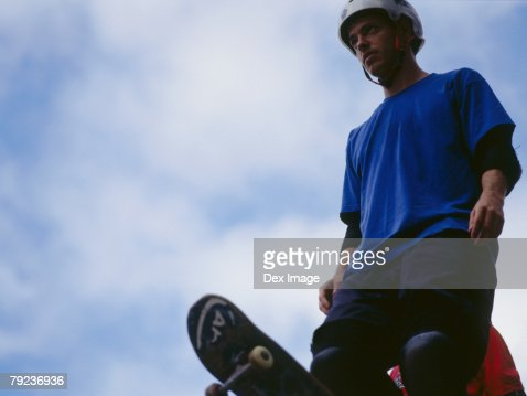 Young male standing on ramp holding skateboard : Stock Photo