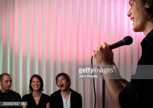 Young male stand-up comedian performing on stage, audience laughing