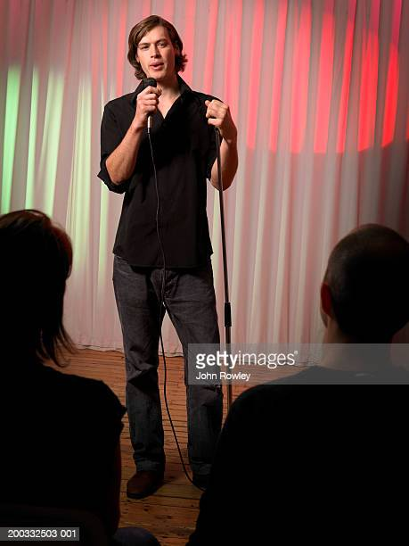 Young male stand-up comedian performing on stage, portrait