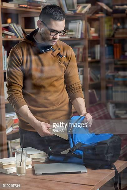 Junge männliche Student Packen Bücher in seinem Rucksack.