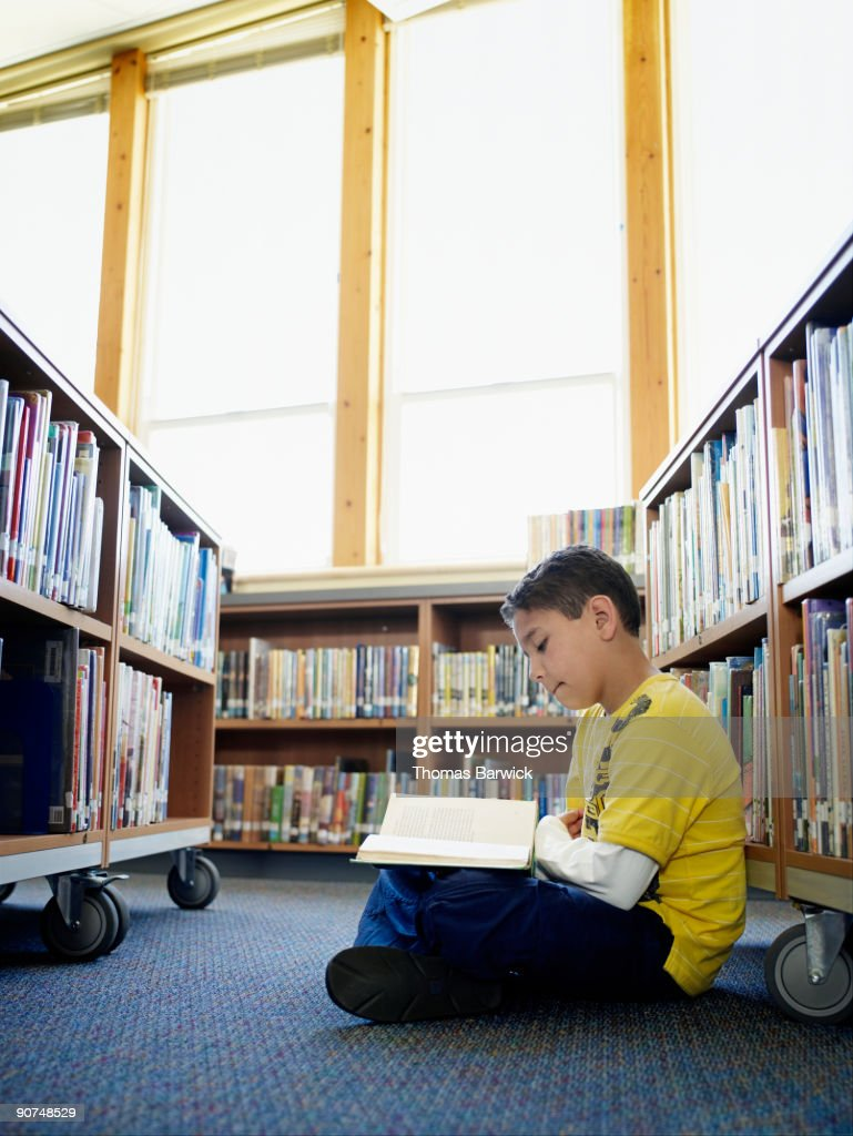 Young male student sitting in aisle of library : Stock Photo