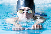 closeup of a male swimmer swimming with a swim board doing leg exercises in an indoor swimming pool - focus on the face