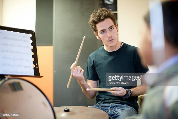Young male teaching boy how to play drum kit