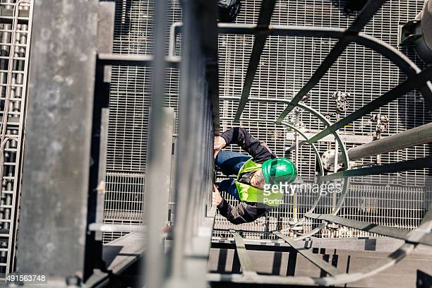 Young male technician climbing ladder in factory