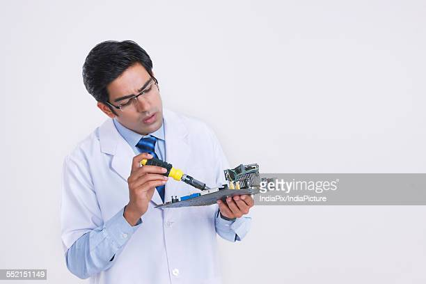 Young male technician repairing circuit board against gray background