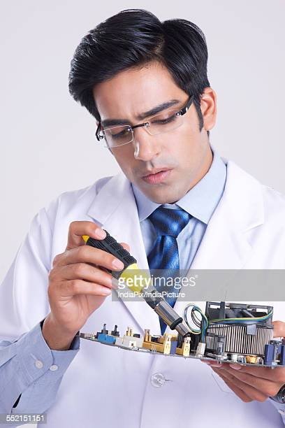 Young male technician working on machine part over gray background