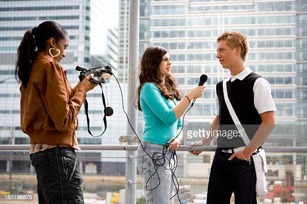 A young male teenager being interviewed by two young females