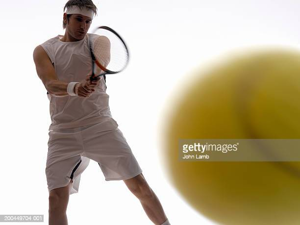 Young male tennis player holding racquet, ball in foreground