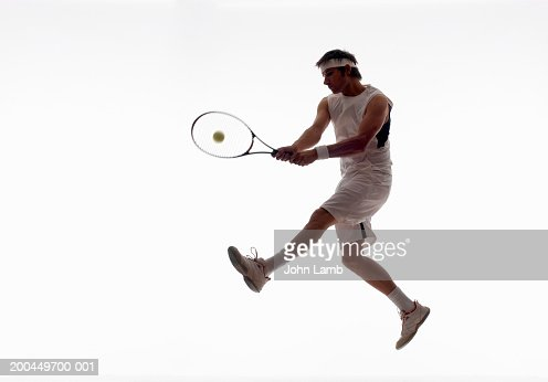 Young male tennis player jumping to hit ball with backhand