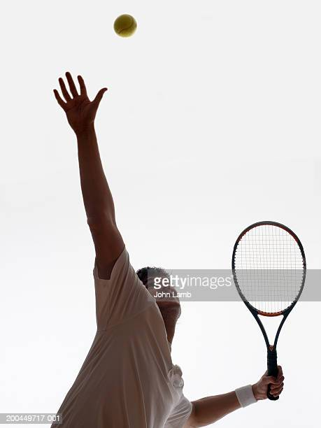 Young male tennis player striking serve