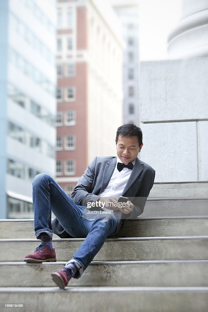 Young male texting while sitting on city steps : Stock Photo