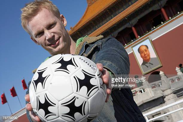 A young male tourist extends a  soccer ball in front of Tiananmen Square in Beijing.