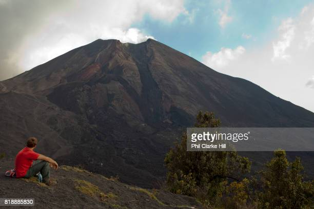A young male traveller looking at Pacaya an active volcano in Guatemala near the old Colonial capital city of Antigua in the Escuintla Department It...