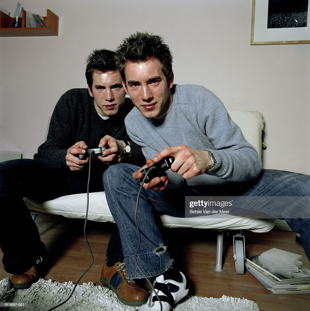 Young male twins playing games console : Bildbanksbilder