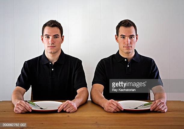 Young male twins sitting at table with empty plates, portrait