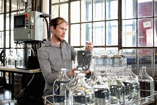 Young male vodka distiller checking demijohn in distillery workshop