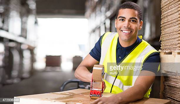 young male warehouse worker packing boxes for shipment