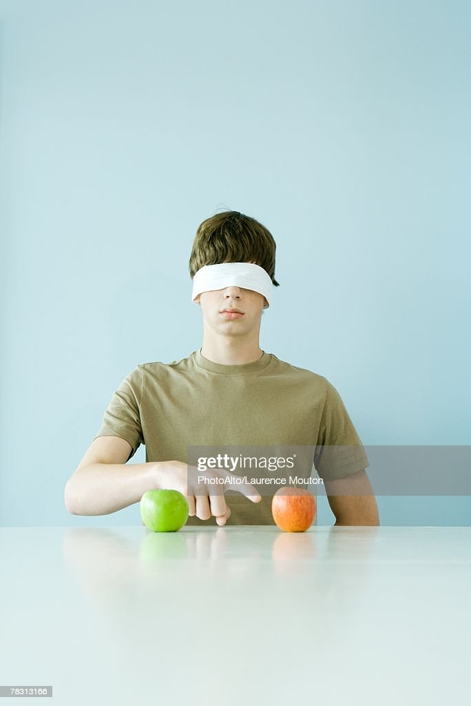 Young male wearing blindfold, pointing to one of two apples