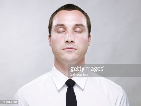Young male, wearing shirt and tie with eyes closed : Stock Photo