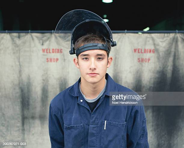Young male welding student outside welding shop, close-up, portrait