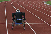 Young male wheelchair track athlete on track, rear view