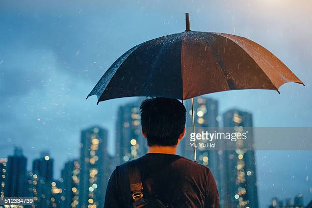 Young male with umbrella looking away at city