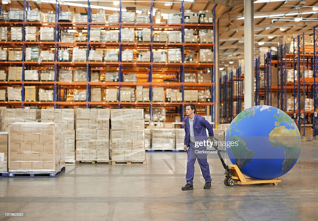 Young male worker pulling hand truck with large blue ball in warehouse : Stock Photo