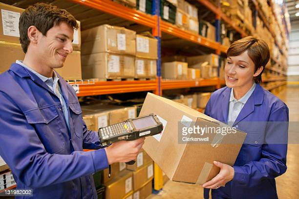 Young male worker scanning barcode while female holding the box