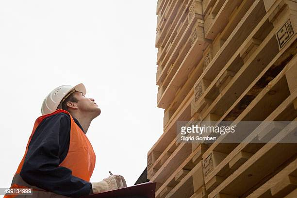 Young male worker with clipboard looking up at pallet tower in timber yard
