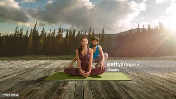 Young male yoga teacher teaches the girl assan