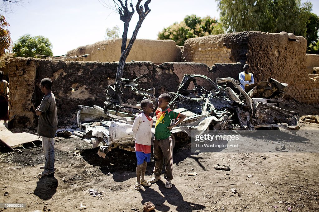 Young Malian boys stand near the wreckage of a vehicle that was destroyed in a French airstrike on January 21, 2013 near Diabaly, Mali. For the last week, French and Malian forces fought to route Islamic militants from the town.