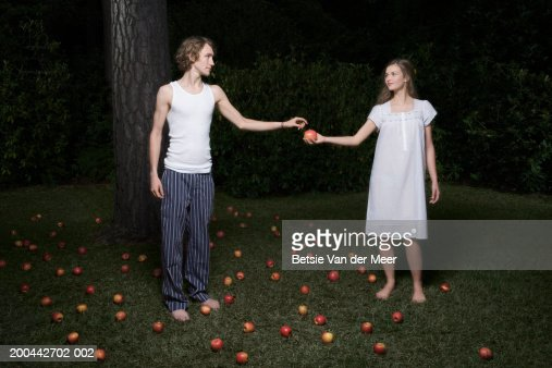 Young man accepting apple from teenage girl (16-18) in garden, night : Stock Photo