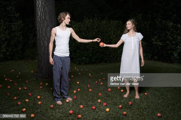 Young man accepting apple from teenage girl (16-18) in garden, night
