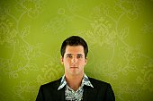 Young man against floral wallpaper.