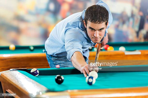 Young man aiming at the ball and playing billiard.