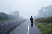 Young man alone walking on sidewalk in mist of early morning. Foggy air. Go away. Back view.