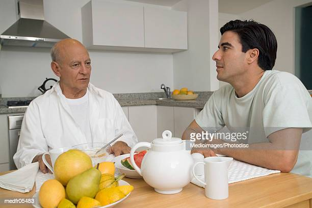 Young man and a senior man sitting together at the breakfast table
