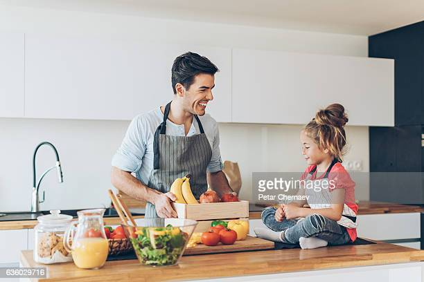 Young man and a small girl in the kitchen