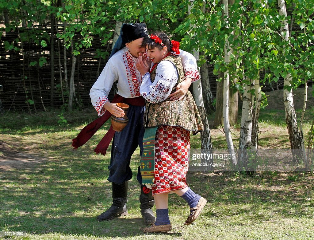 Young man and a woman in Ukrainian traditional clothes during folk Easter Tradition of pouring water called 'Pouring Monday' in open air Cossack village 'Mamaeva Sloboda', Ukraine,on May 02, 2016. The tradition of pouring water when single guys pour unmarried girls by water is celebrated on the first Monday after Orthodox Easter.