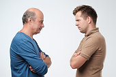 Mature father and son looking on each other face to face. They quarreled. To make claims and reproaches